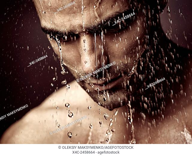 Pensive troubled man face under pouring shower dramatic emotional portrait