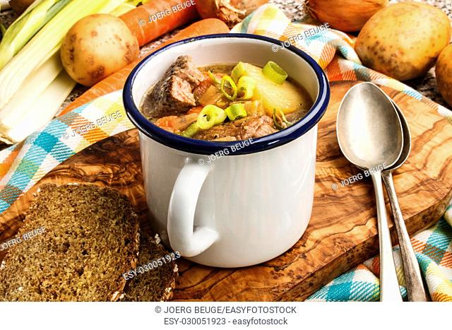 irish lamb stew served in an blue and white enamel cup on a wooden board