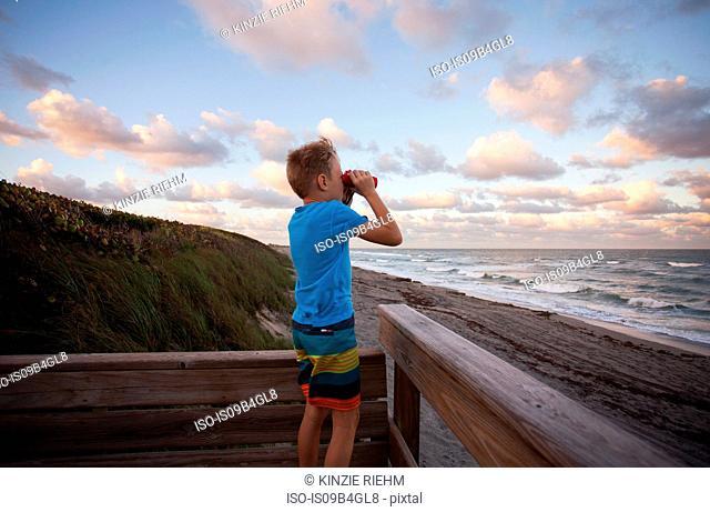 Boy at beach looking at view through binoculars, Blowing Rocks Preserve, Jupiter, Florida, USA