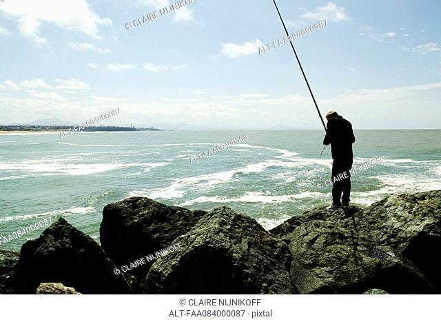 Fisherman and his fishing rod, port of Biarritz on the horizon