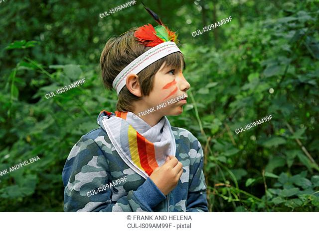 Boy dressed up in face paint and playing in forest