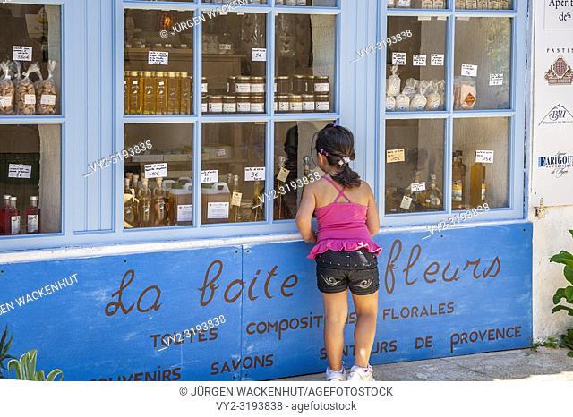 Girl at the window of a souvenir shop, Ramatuelle, Var, Provence-Alpes-Cote d`Azur, France, Europe