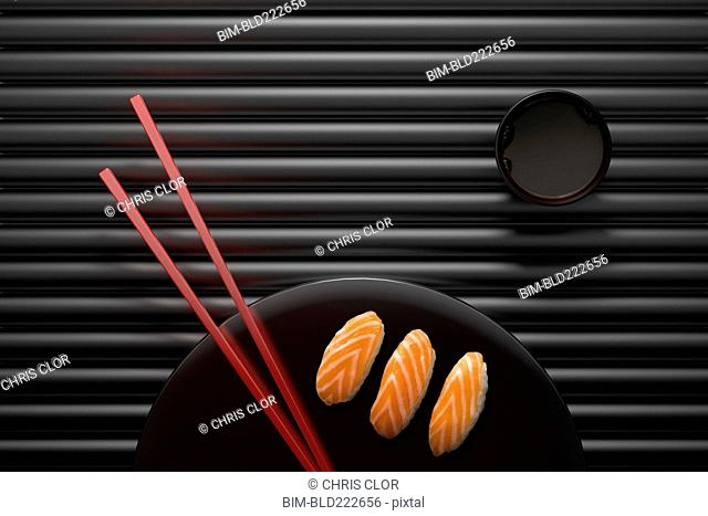 Chopsticks and sushi on round plate with dipping sauce