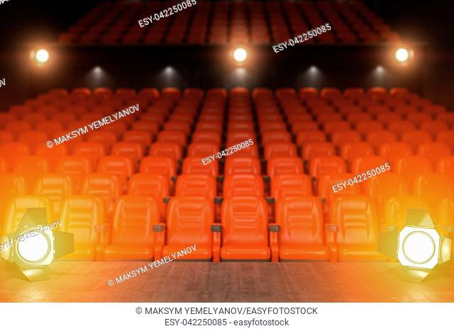 View from the stage of concert hall or theater with red seats and spot light. 3d illustration