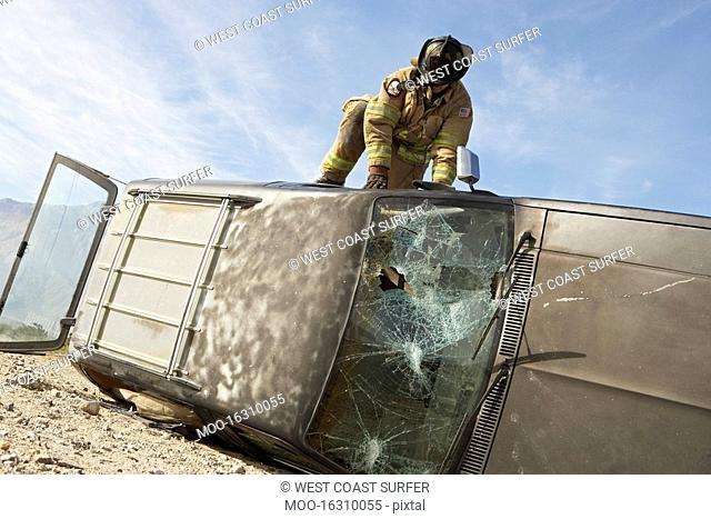 Firefighter trying to get into crashed car