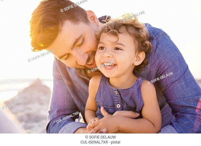 Portrait of father and toddler daughter at beach, Tuscany, Italy