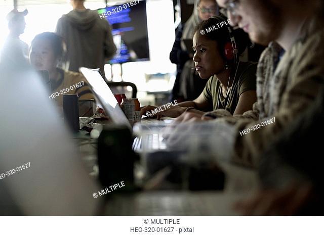 Focused hackers working hackathon at laptops in dark office