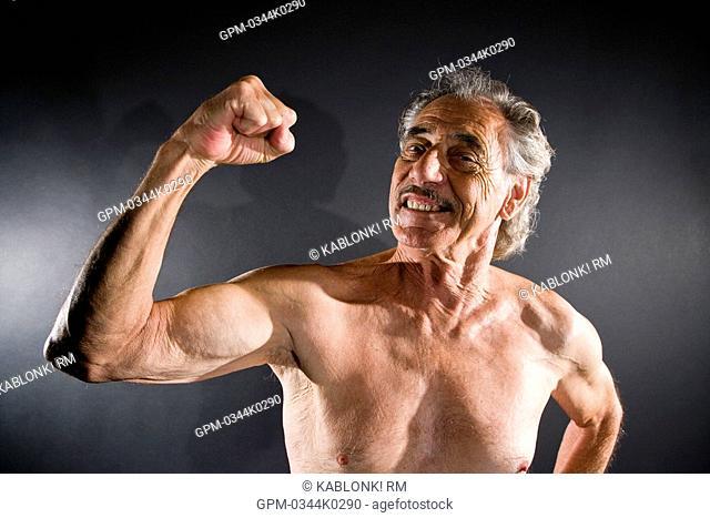 Senior man flexing muscles against gray background