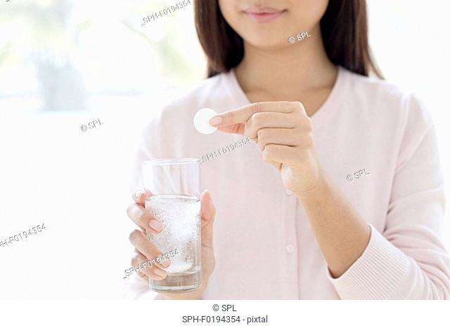 Woman holding tablet and glass of water
