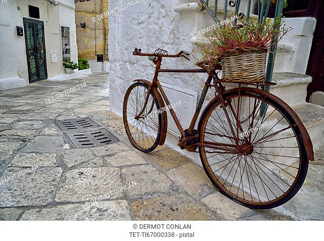 Old rusty bicycle with flower basket by steps