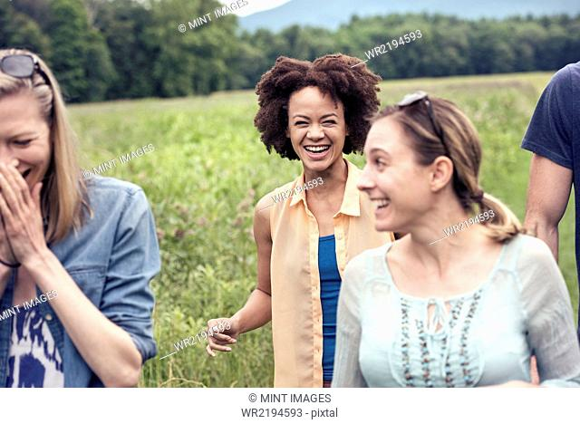 A group of women walking through a meadow in the countryside laughing