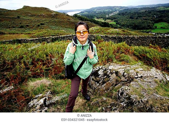 An East Asian Woman, looking at the camera, hiking in Lake District, Cumbria, UK. Grasmere lake in the back ground