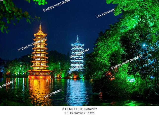 The sun and moon pagodas at Shan lake illuminated at night, Guilin, Guangxi, China