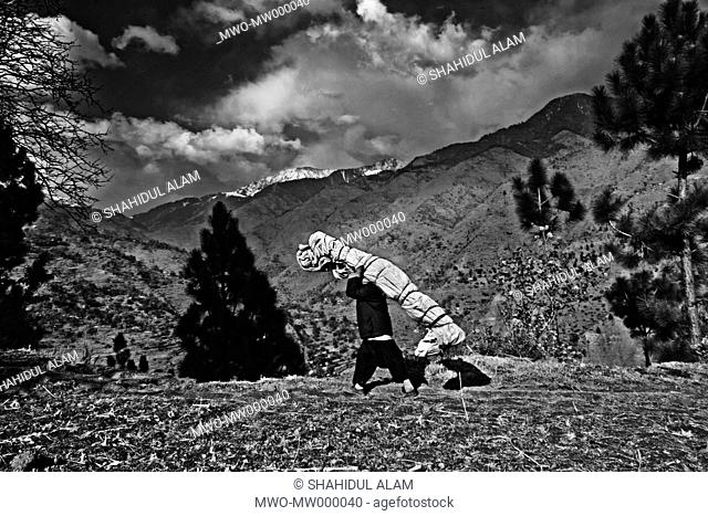 After the devastation of the 2005 Kashmir earthquake, a man carries a tent up the mountain to his home near the snowline, in Narak, Iran December 1, 2005