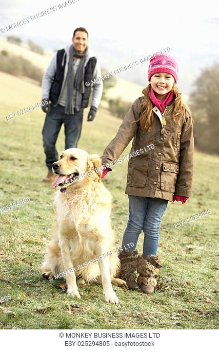 Father and daughter walking dog in country