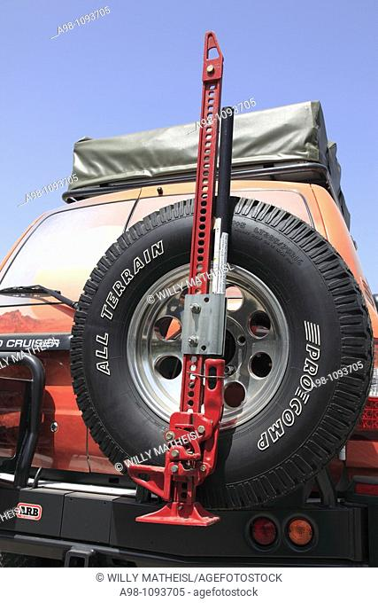 car-jack on spare tire of a Toyota Land Cruiser four wheel drive in the Sultanate of Oman, Middle East