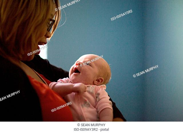 Young woman and baby daughter smiling at each other