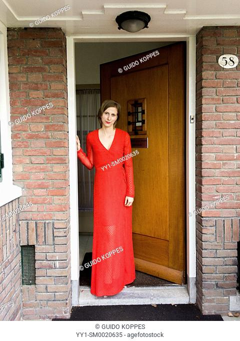 Tilburg, Netherlands. Portrait young adult woman wearing a red dress standing in an opened domestic front door