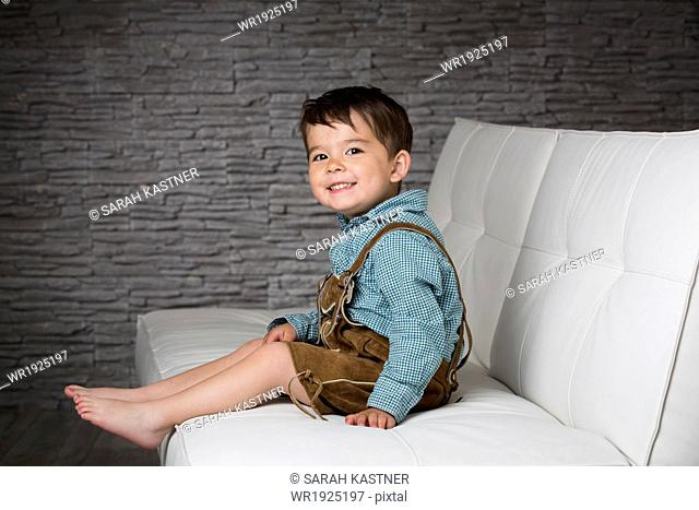 Little boy with leather pants on a sofa