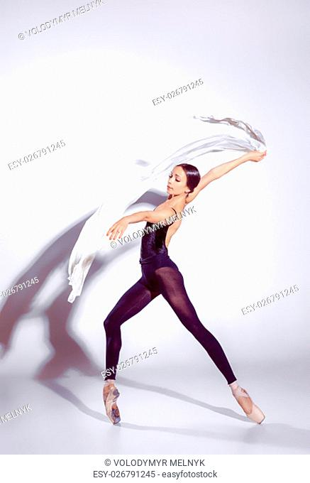 Ballerina in black outfit posing on toes, studio gray background