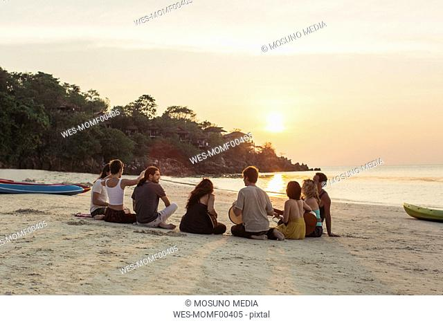 Thailand, Koh Phangan, group of people sitting on a beach with guitar at sunset