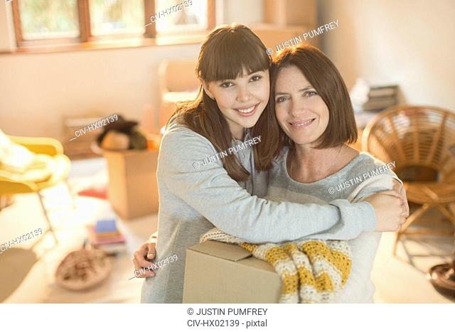 Portrait smiling mother helping young adult daughter move into new apartment