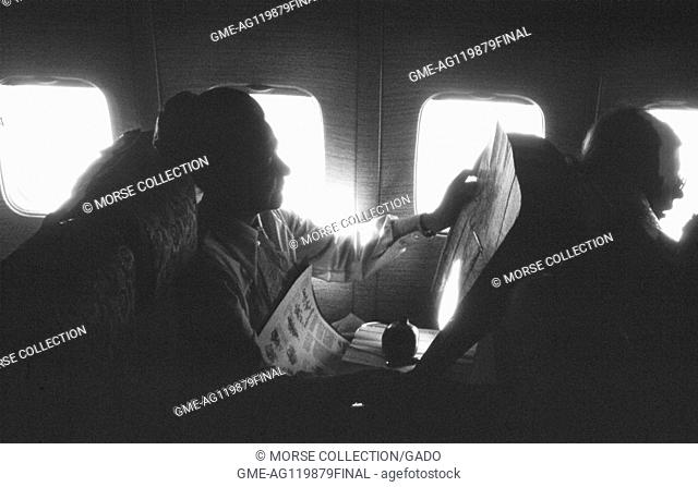 View of a woman reading a newspaper at her window seat on a Turkish Airlines flight, in Istanbul, Turkey, November, 1973