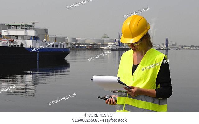Female docker in an industrial harbor giving instructions from her clipboard via a walkie talkie