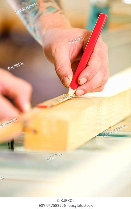 Craftsman measures the length of a wooden plank. Makes a line with a pencil before sawing