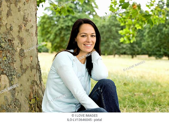 A young woman sitting beneath a tree, smiling
