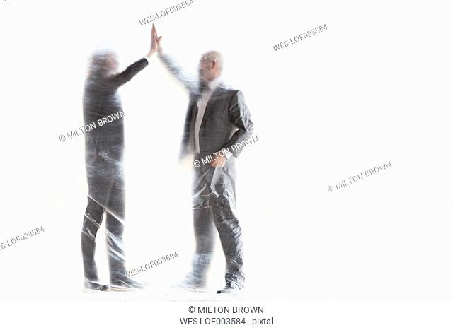 Two businessmen behind foil high fiving
