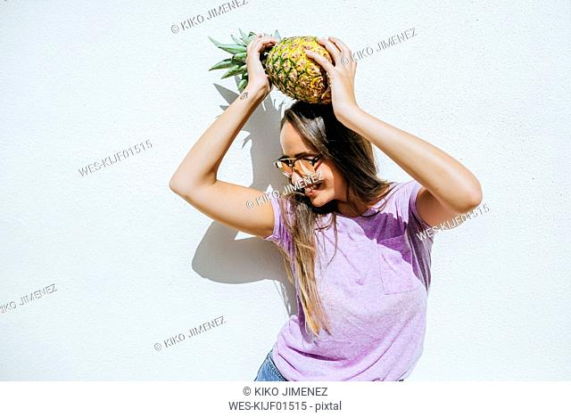 Happy young woman holding pineapple in front of white wall