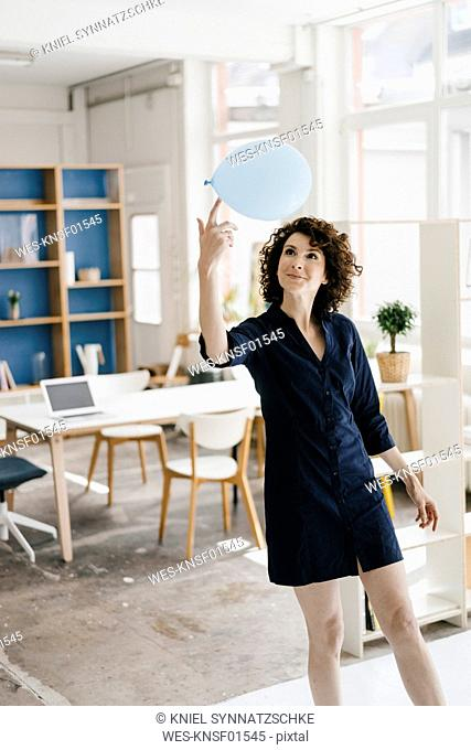 Businesswoman in office balancing balloon on finger