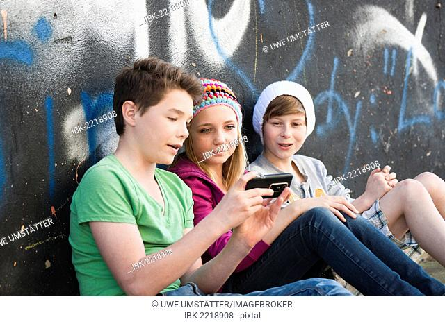 Three teenagers with a tablet PC sitting in front of a wall with graffiti
