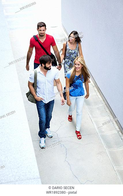 Group of university students walking along campus