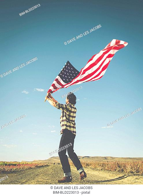 Hispanic man standing in desert waving American flag