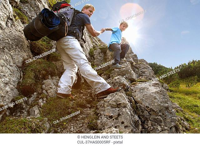 Father and son hiking on rocky terrain