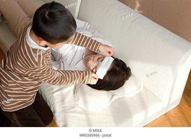 Son sticking cooling sheet on mother's forehead