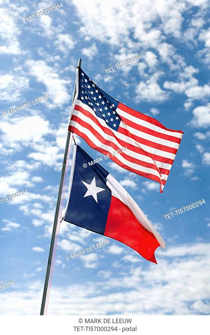 American and Texas flags against cloudy sky
