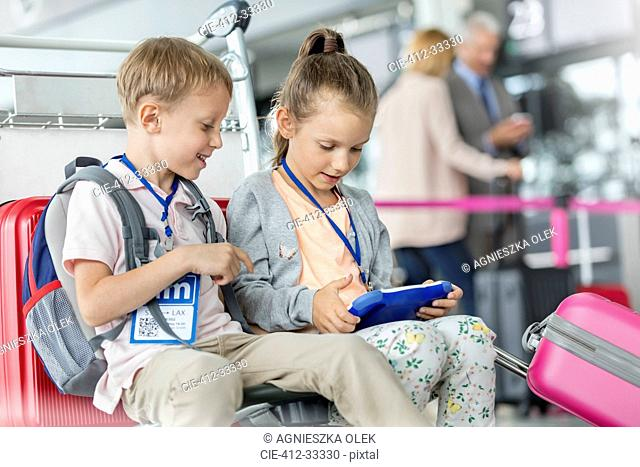 Brother and sister using digital tablet in airport departure area
