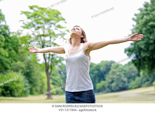 Portrait of a young woman with arms outstretched in the park