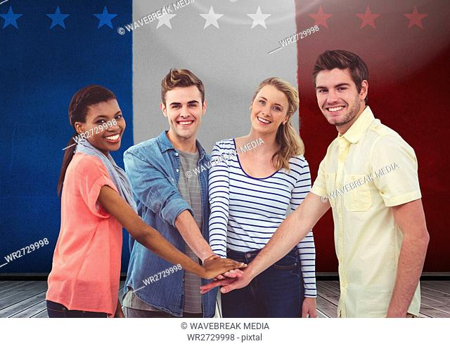 Friends with their hands stacked against french flag in background