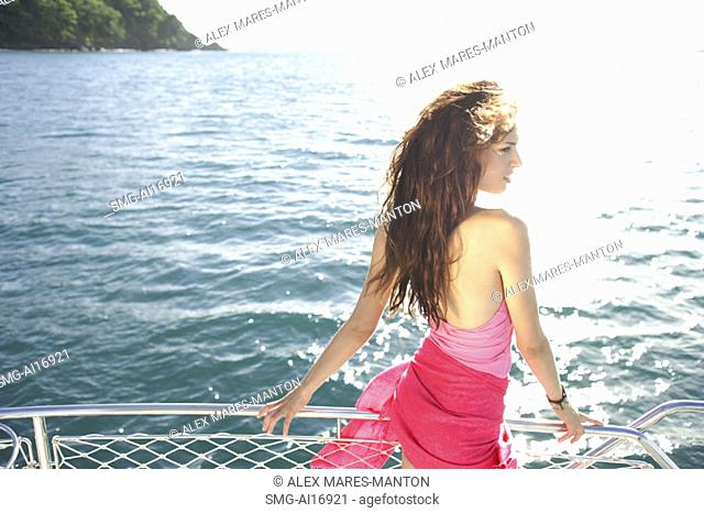 Woman on boat, standing next to railing, side view