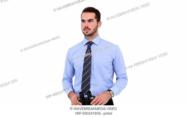 Young businessman looking through binoculars on white background