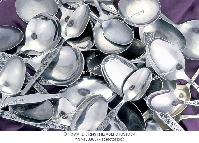close up image of a pile of silver spoons