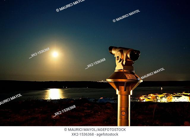monocular looking the full moon in Torre de Fornells, Menorca, Illes Balears, Spain
