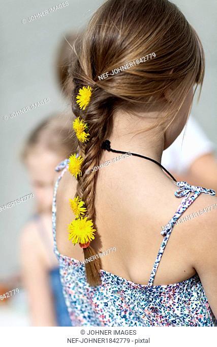 Girl with dandelion flowers in braid