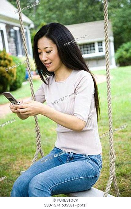 Woman on rope swing and text messaging