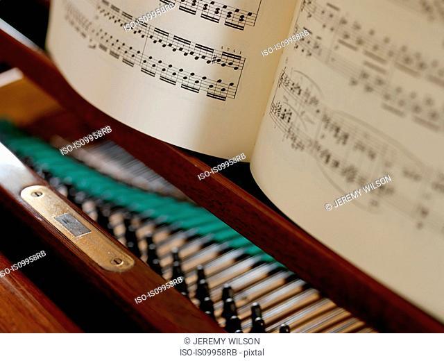 Sheet music and piano strings, close up