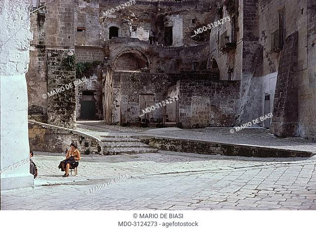 Seated woman relaxing in a small square of Matera. Matera, 1978